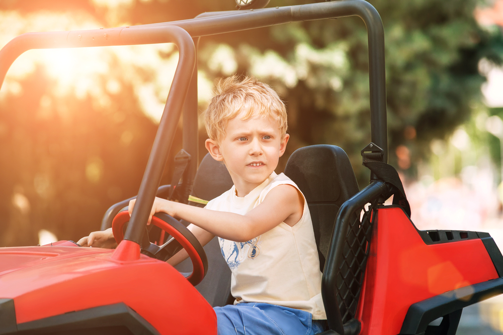 Boy driving an electric car in the park
