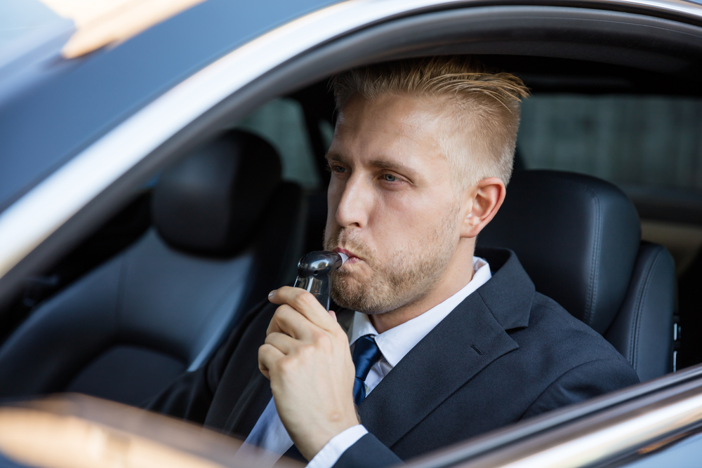 man using breathalyzer in car