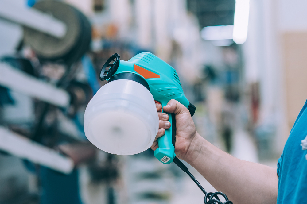 A man holds an electric spray gun in his hand