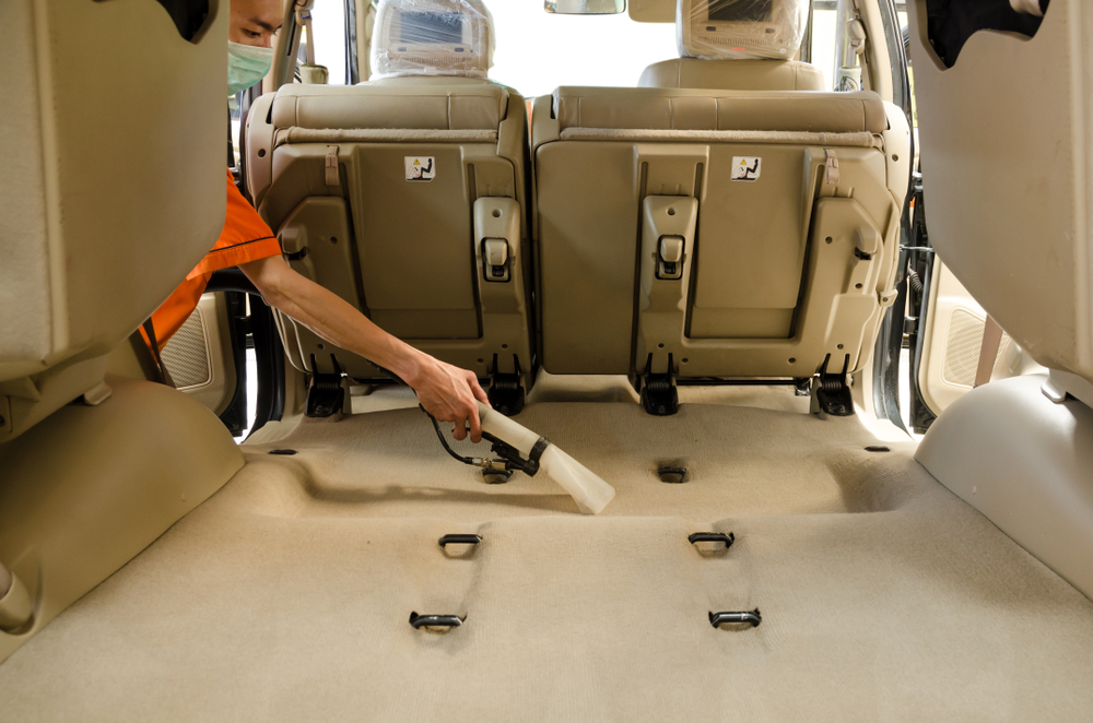 cleaner vacuuming the car carpet
