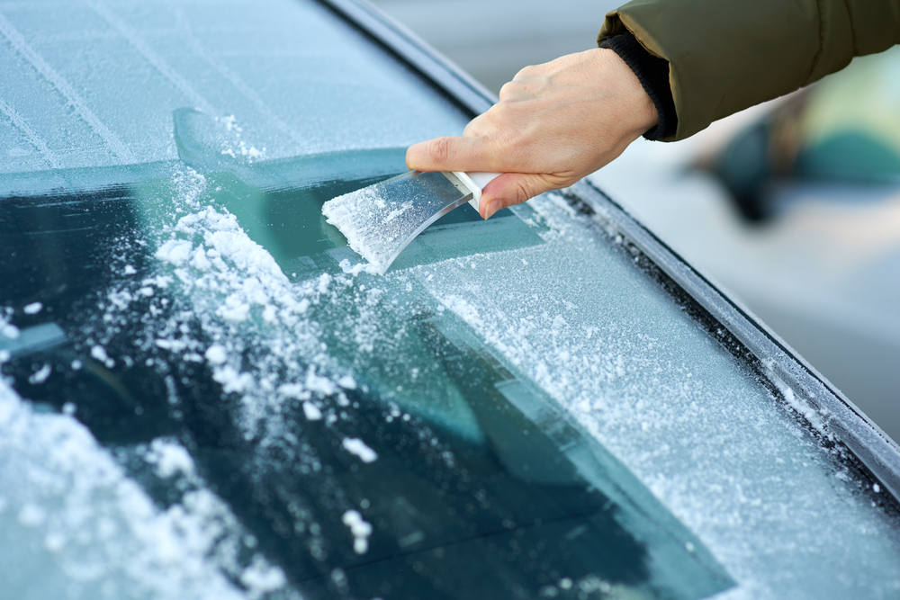 close up of ungloved man's hand scraping ice off of windshield, green puffer coat sleeve showing