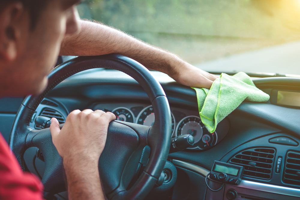 man trying to reach bottom of interior windshield with microfiber towel
