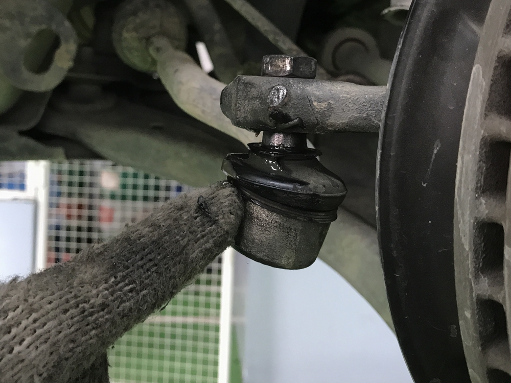 a greased tie rod end attached to a car's rotor
