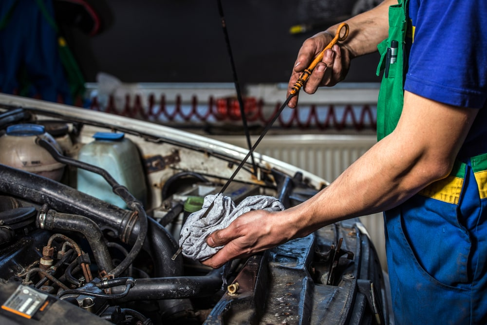 Mechanic checking the oil level in a car