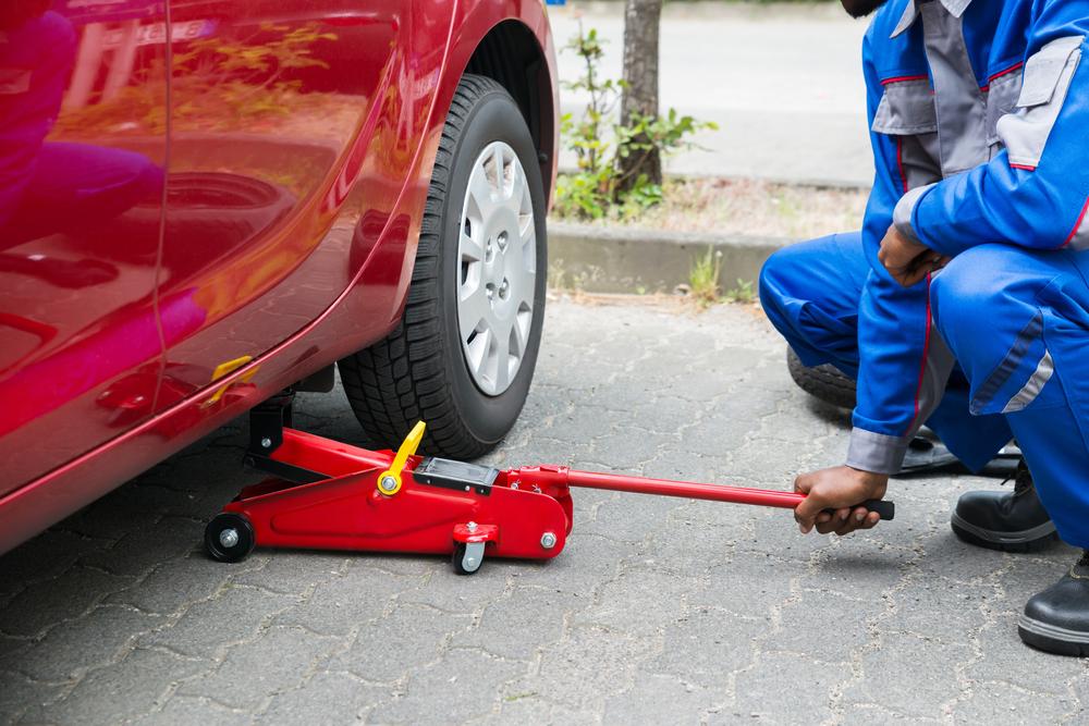 kneeling mechanic using hydraulic jack