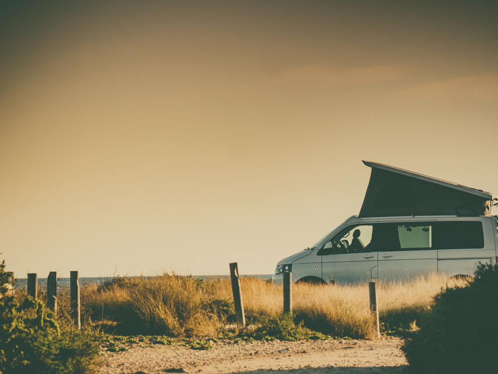 A hard shell roof top tent on a camper van