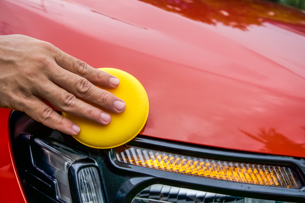 hand waxing car with yellow pad