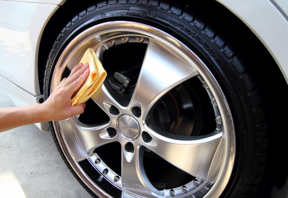 woman buffing chrome polish on wheels