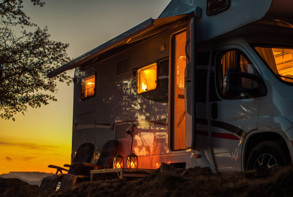 RV with the lights on at sunset