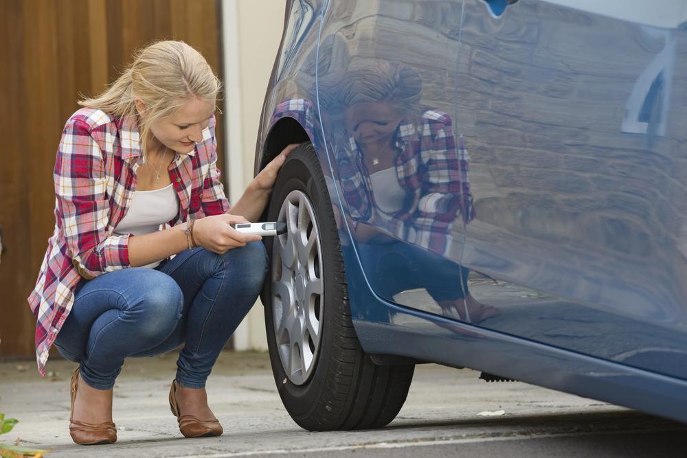 Woman using a tire pressure gauge