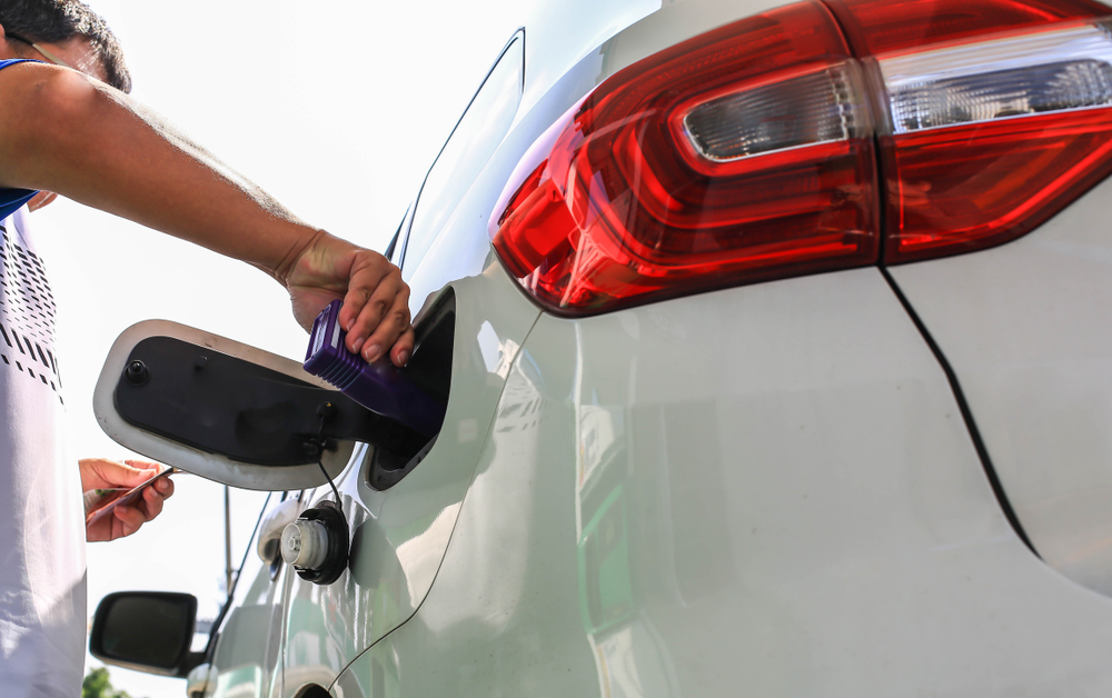 Man pouring fuel additive into a white car