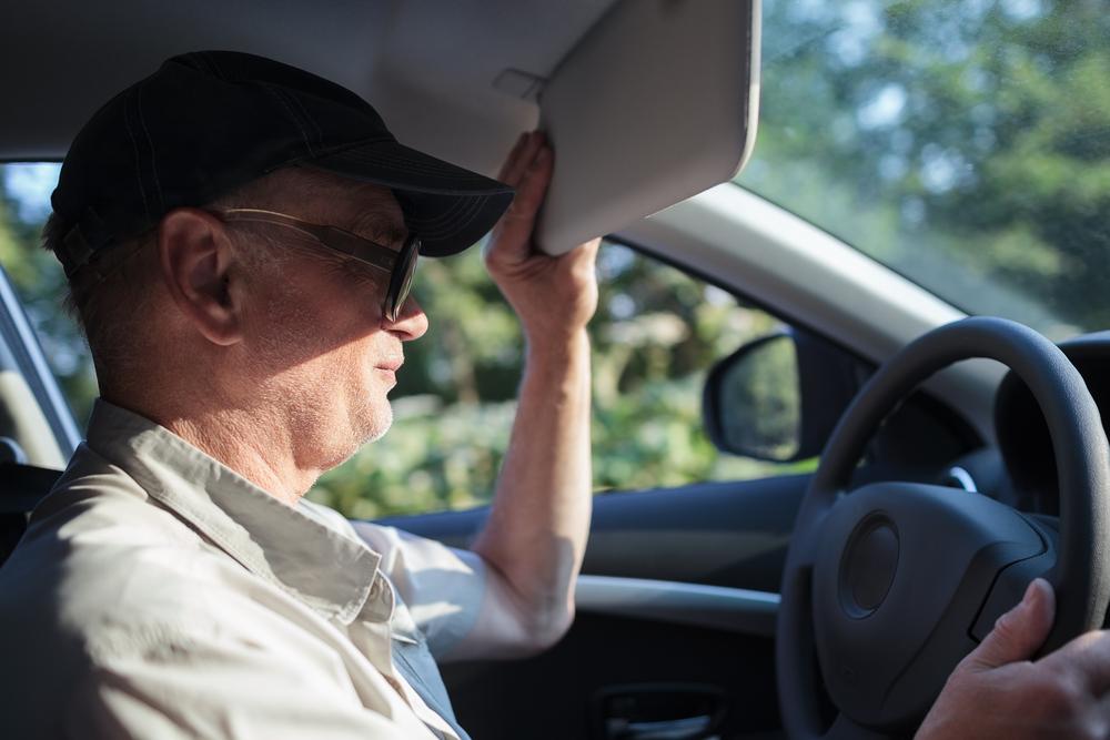 man adjusts car sun visor