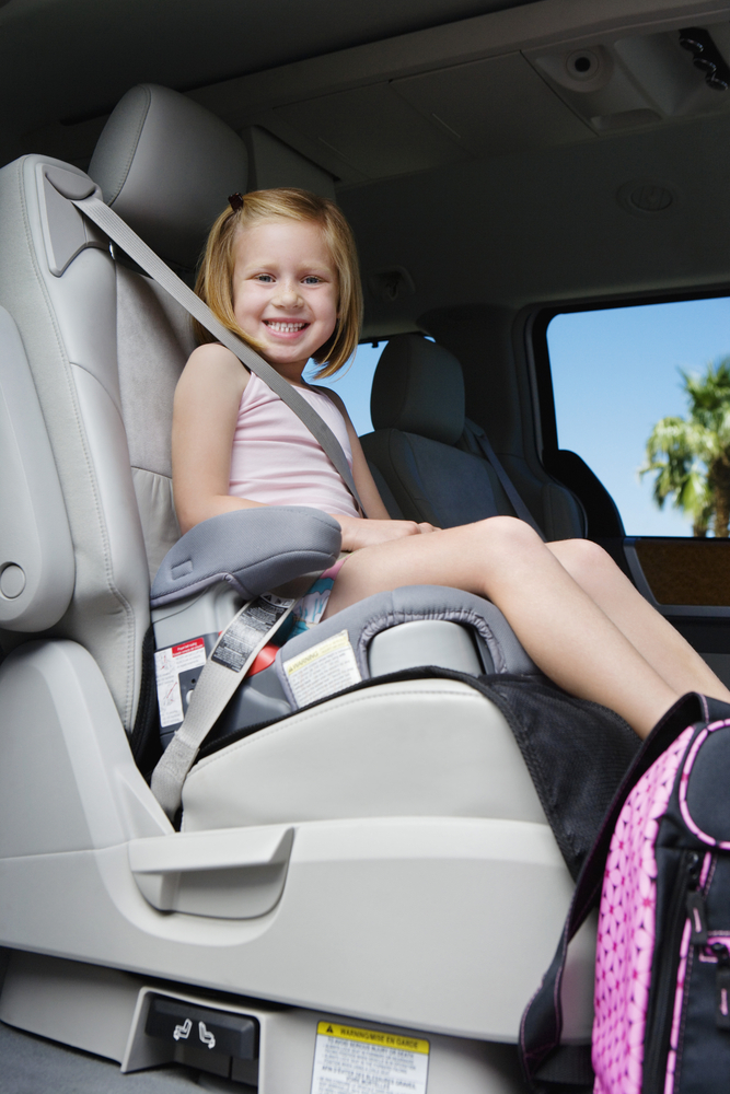 girl smiling in a booster seat