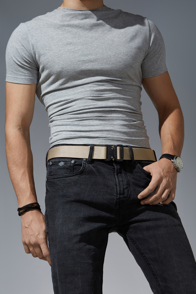 man wearing gold-colored tactical belt