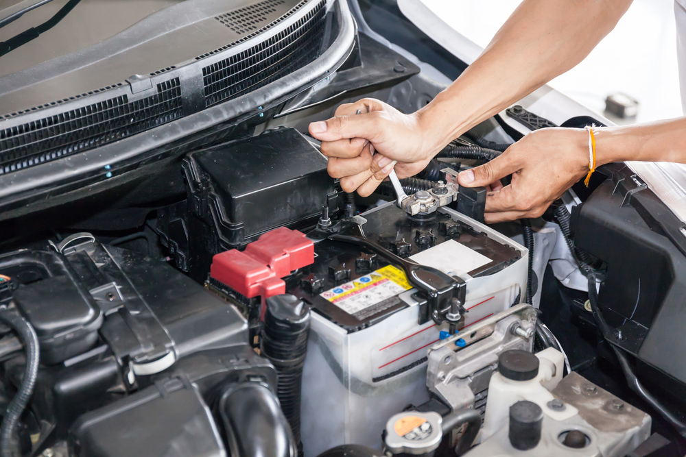 mechanic changes a vehicle battery