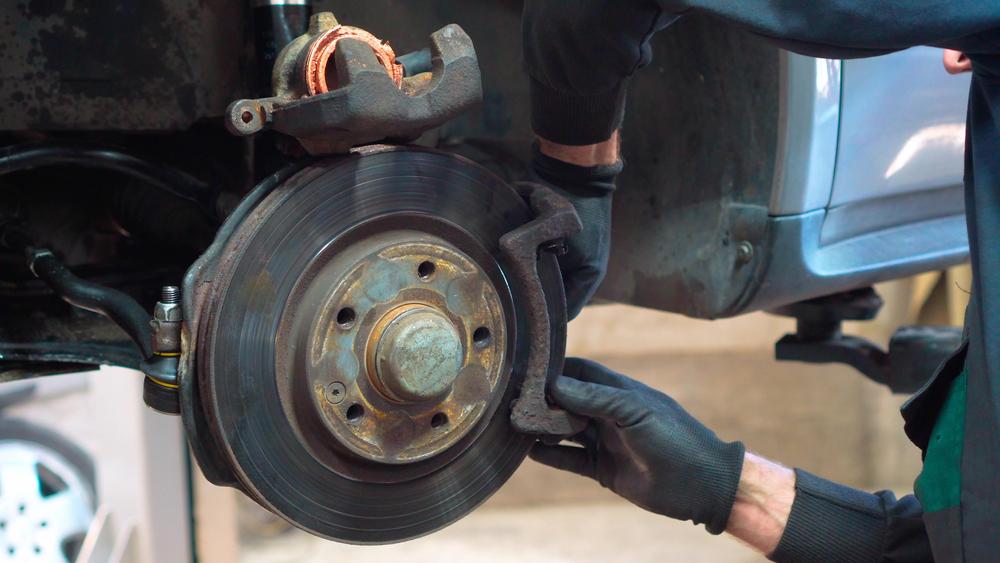 professional repairing a brake