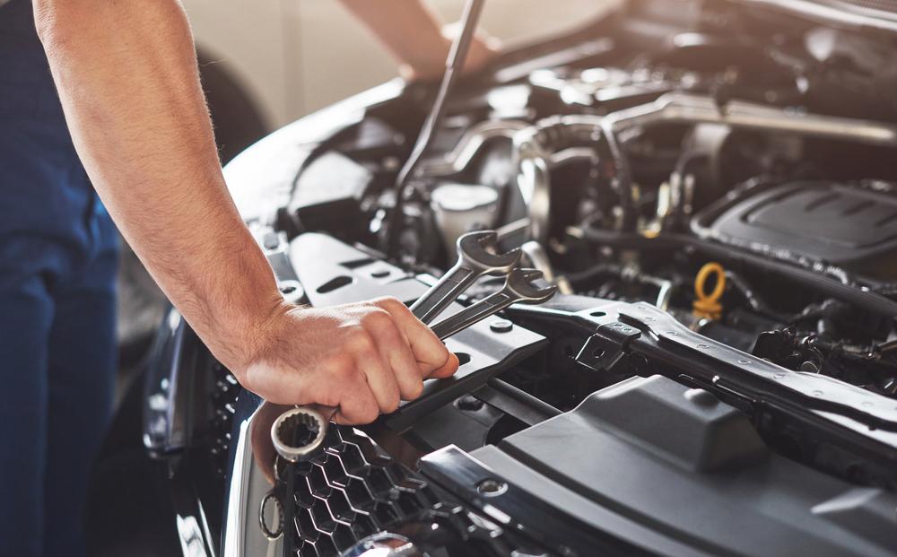 A car mechanic repairing a vehicle's engine