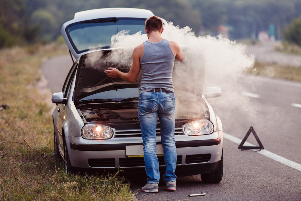 driver attends to smoking car hood