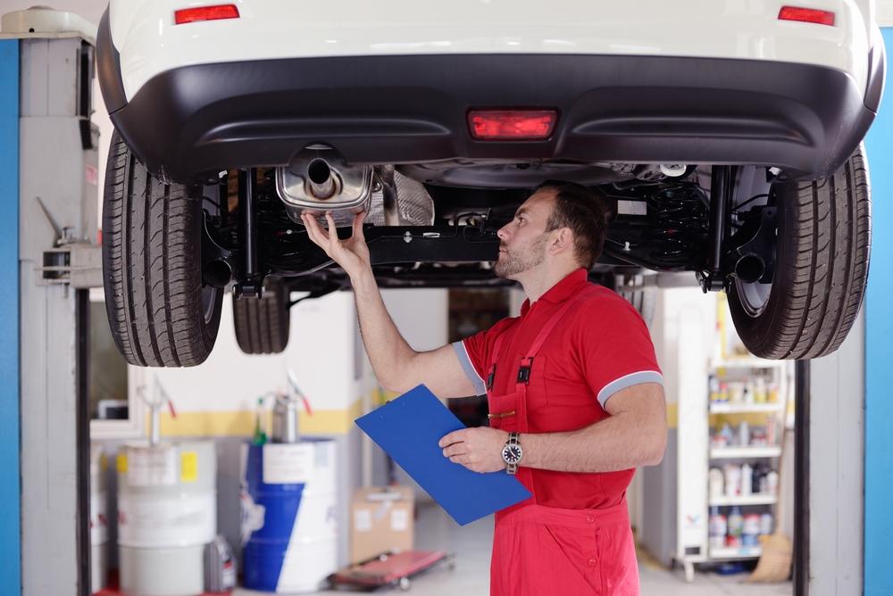 mechanic inspecting car exhaust