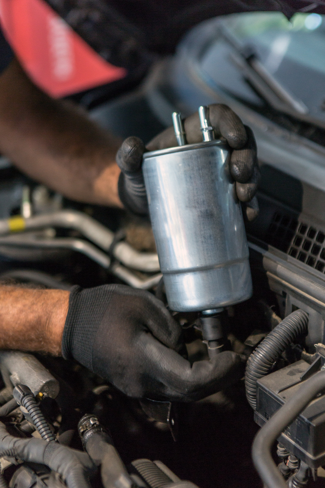a mechanic holding a fuel filter