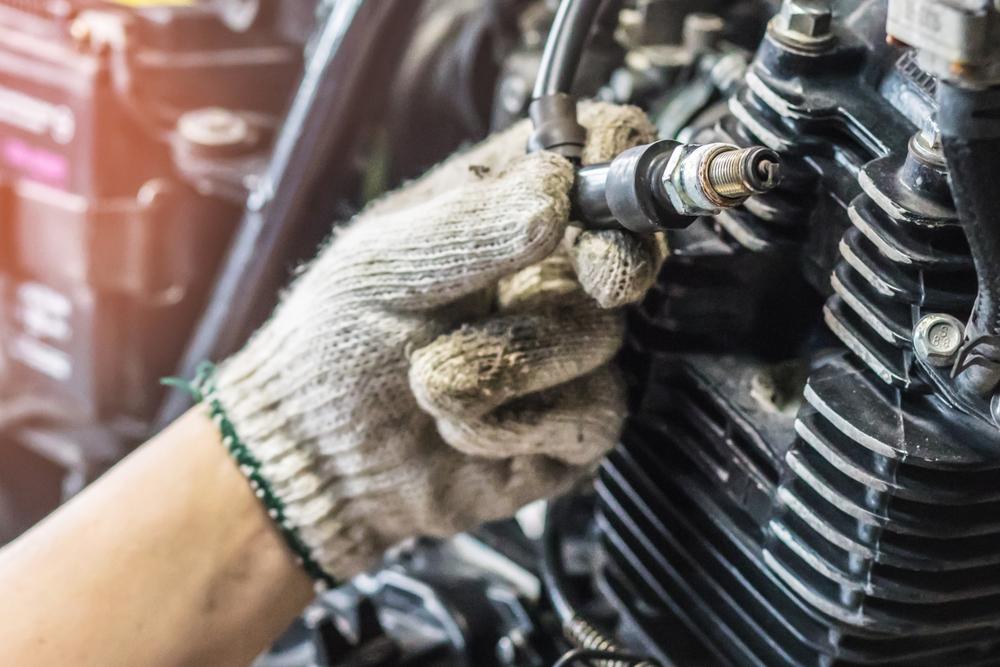 a mechanic inspects a spark plug