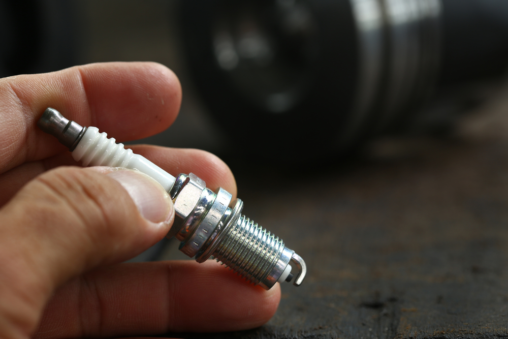 a person holding a new spark plug