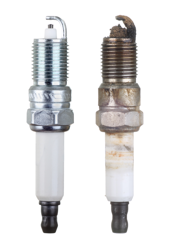 an old spark plug and a new one side by side