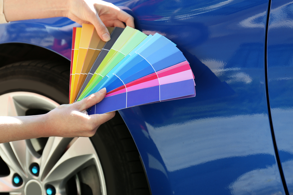 holding color samples up to a car