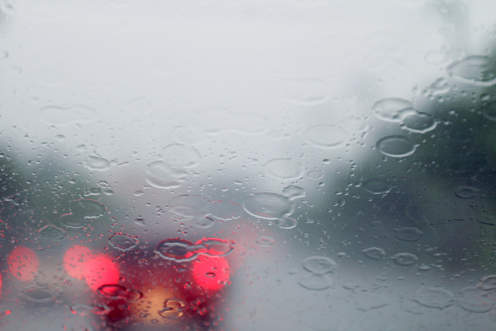 looking through a hazy rain covered windshield in traffic