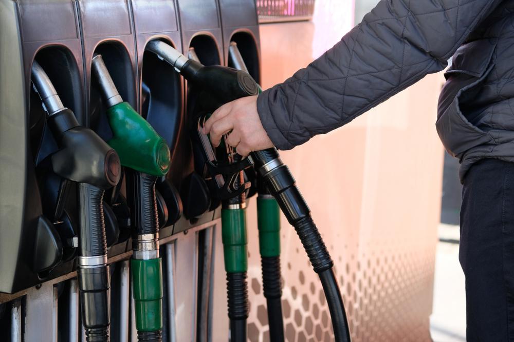 man holding pump at gas station
