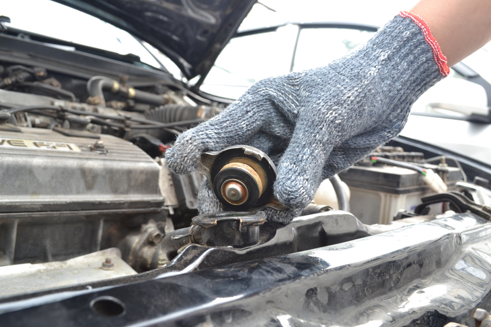 mechanic checking radiator cap