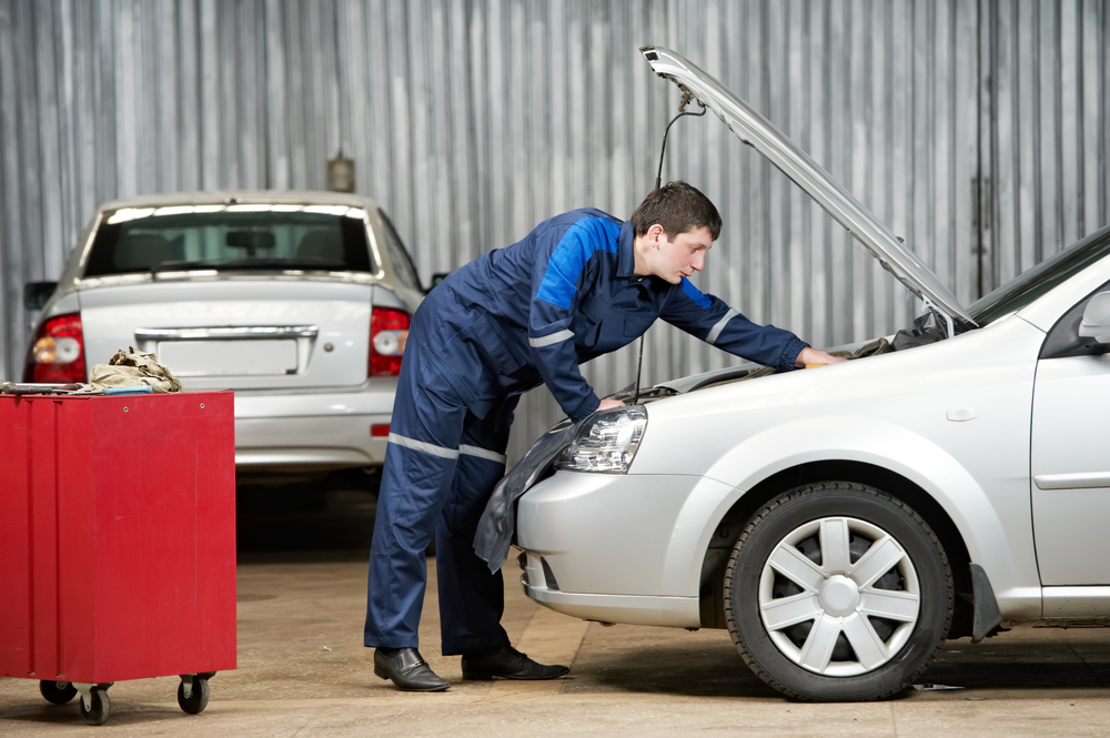 mechanic inspects a vehicles motor