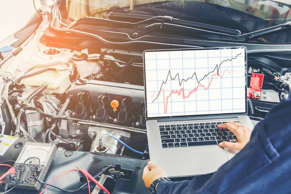 mechanic uses laptop to diagnose fuel issues
