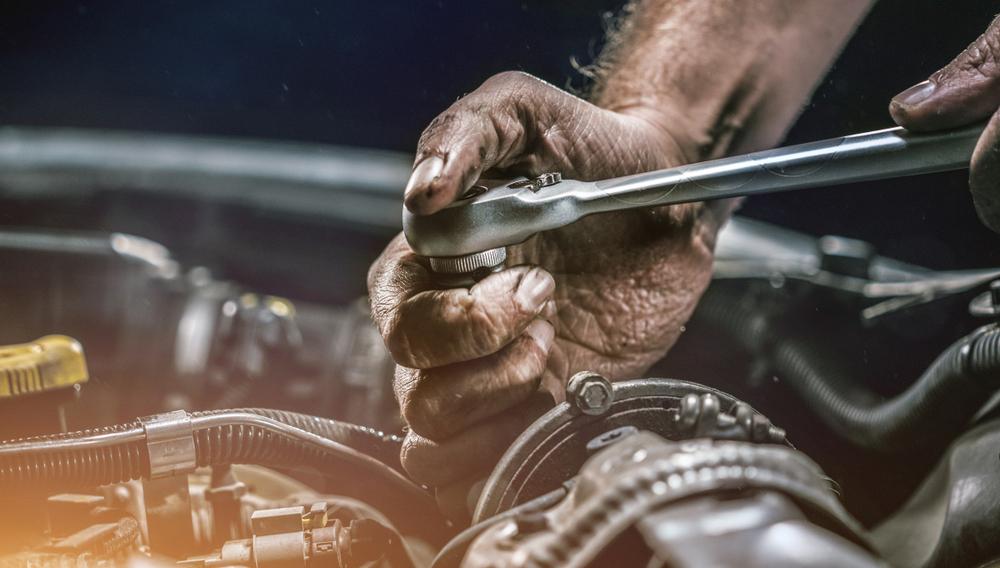 mechanic using a ratchet on engine