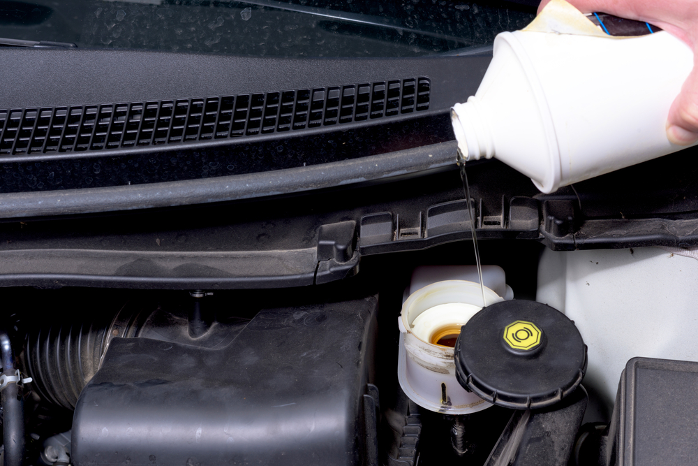 pouring dot brake fluid into a master cylinder