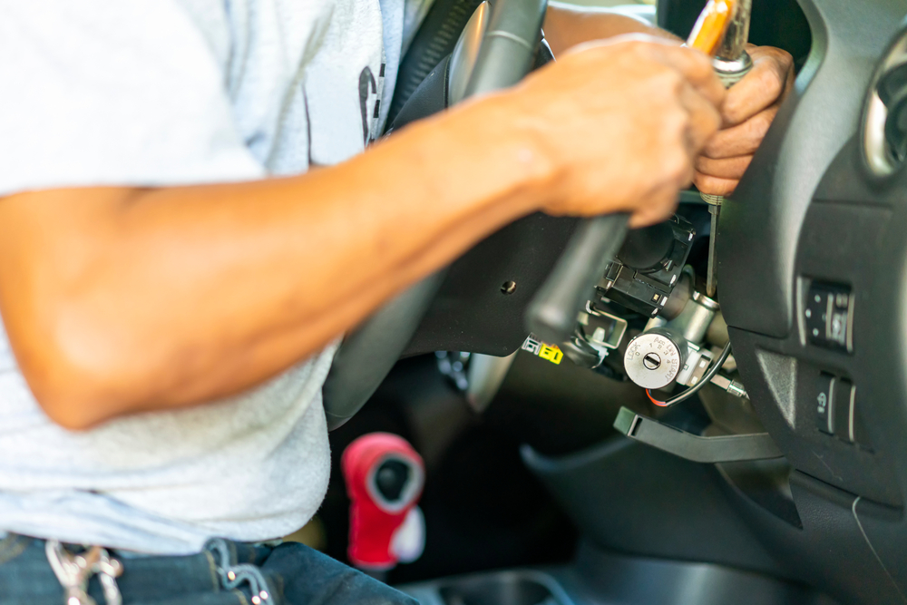 man working on steering column with hammer and screwdriver