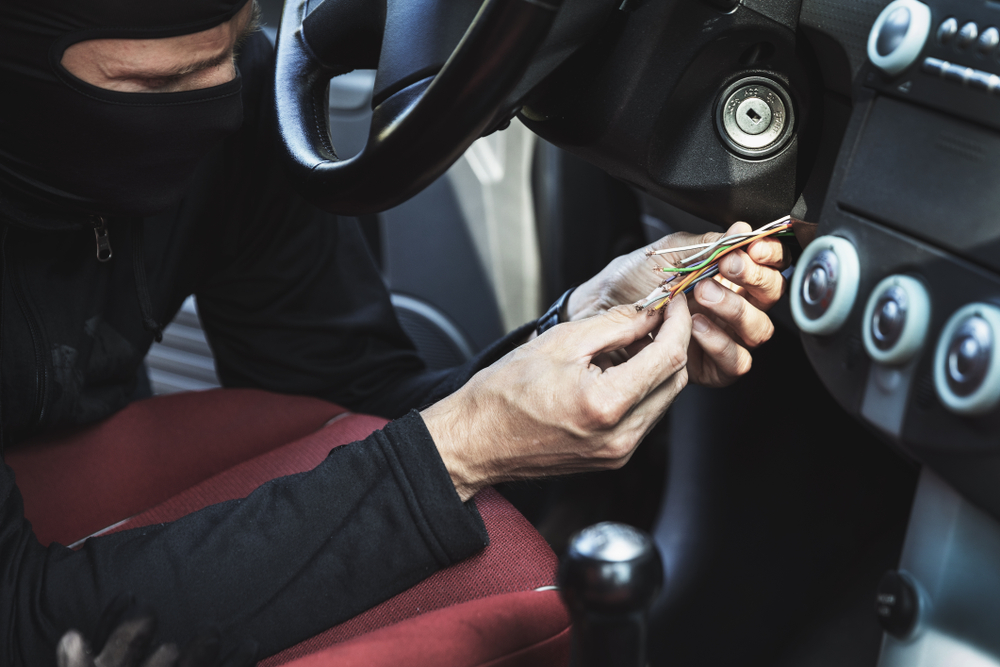 masked man fiddling with exposed steering wheel wires