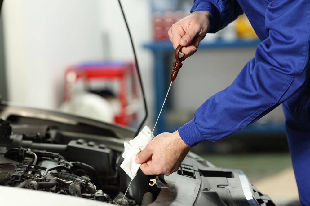 mechanic checking oil level