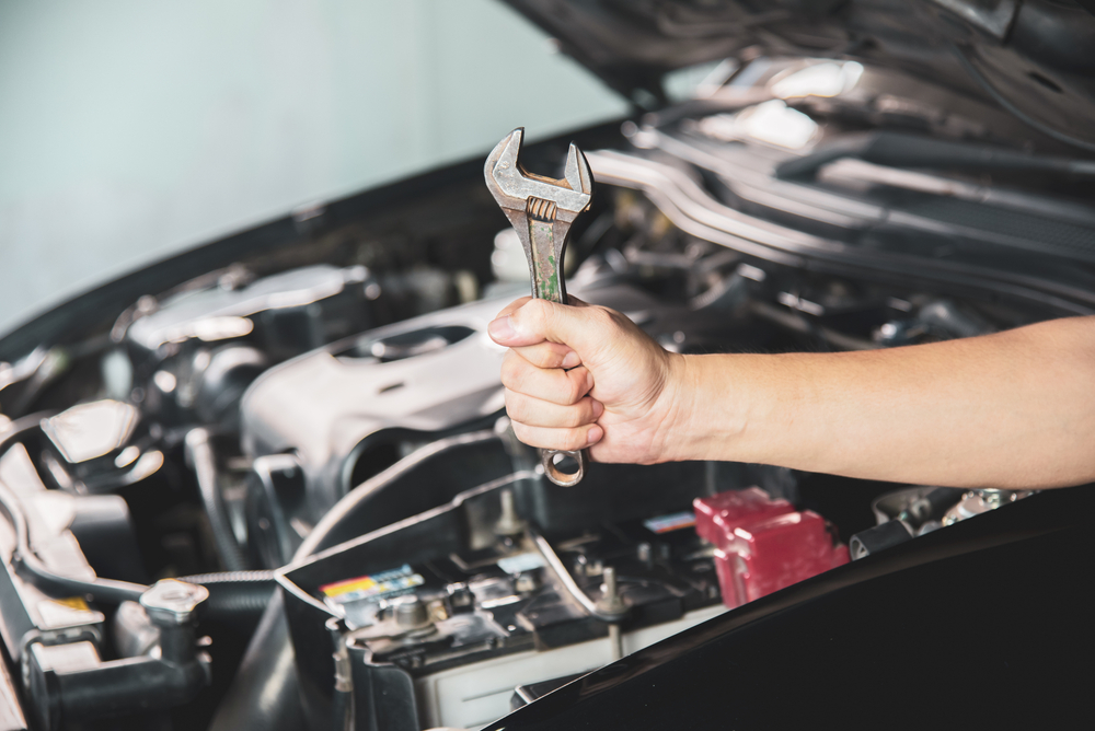 mechanic holding a wrench in front of a car
