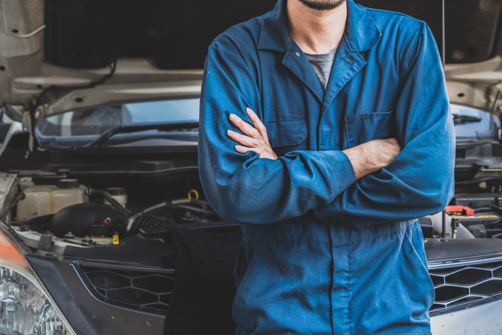 mechanic standing in front of a car