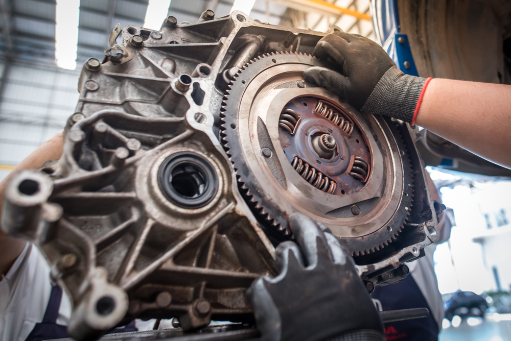 a mechanic fitting a dual mass flywheel to the engine