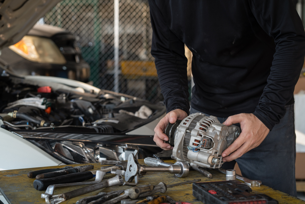 alternator being worked on by mechanic