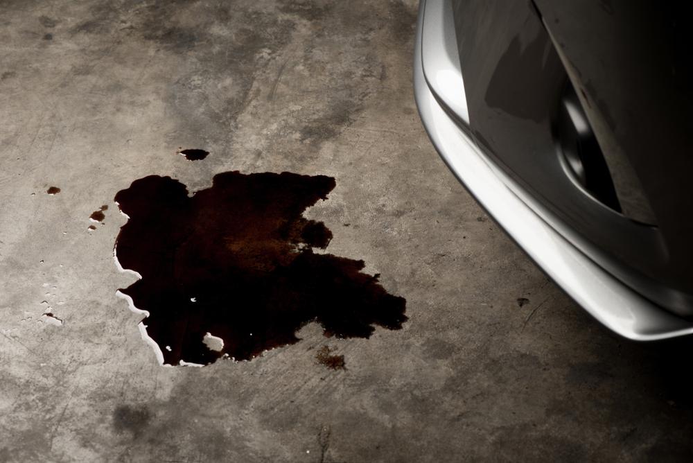 reddish brown fluid leaking from under hood of car