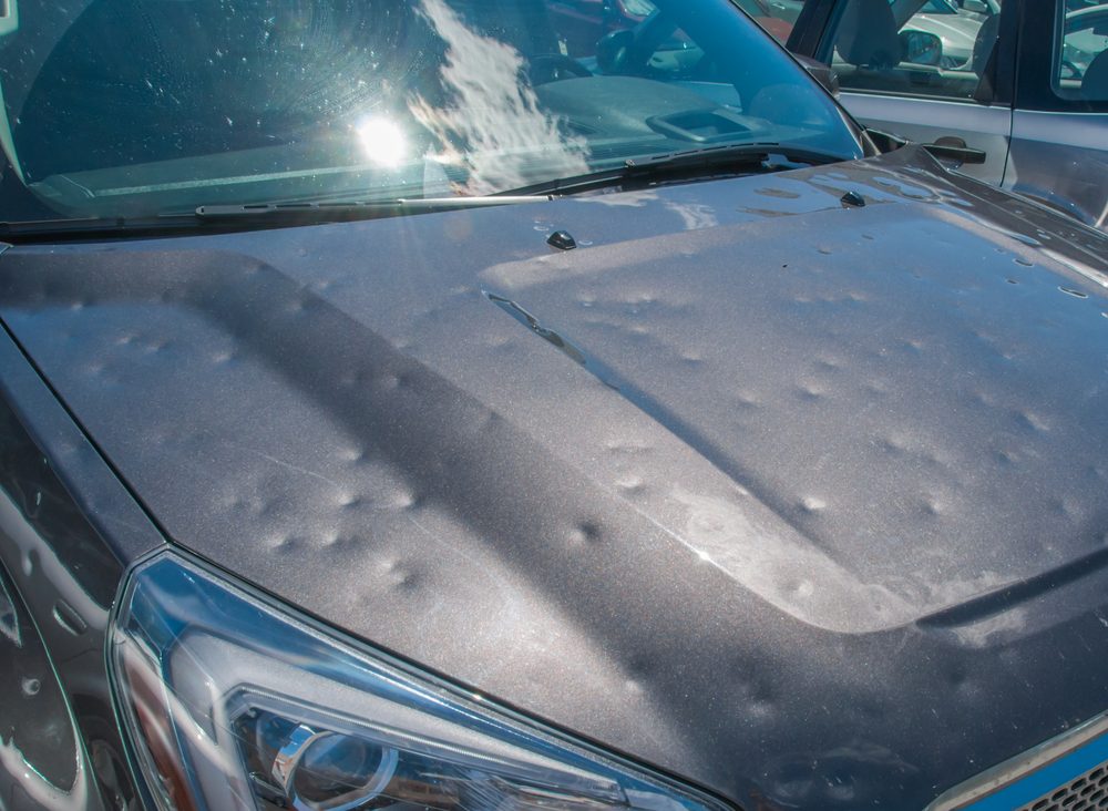 a vehicle hood full of small round dents from hail