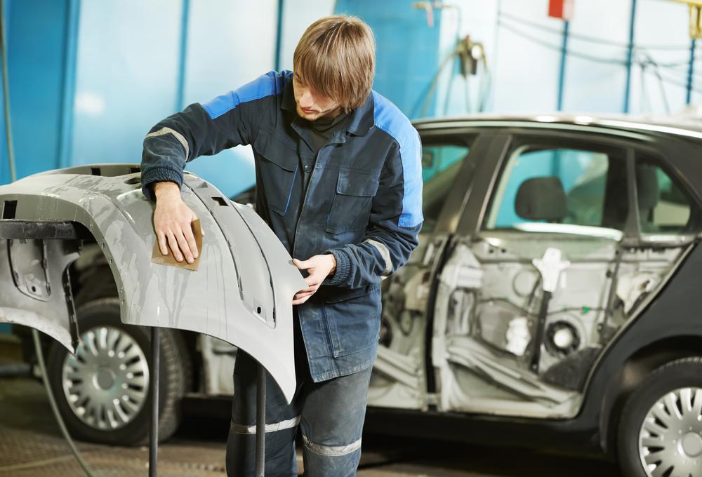auto body technician preparing a new rear bumper for installation