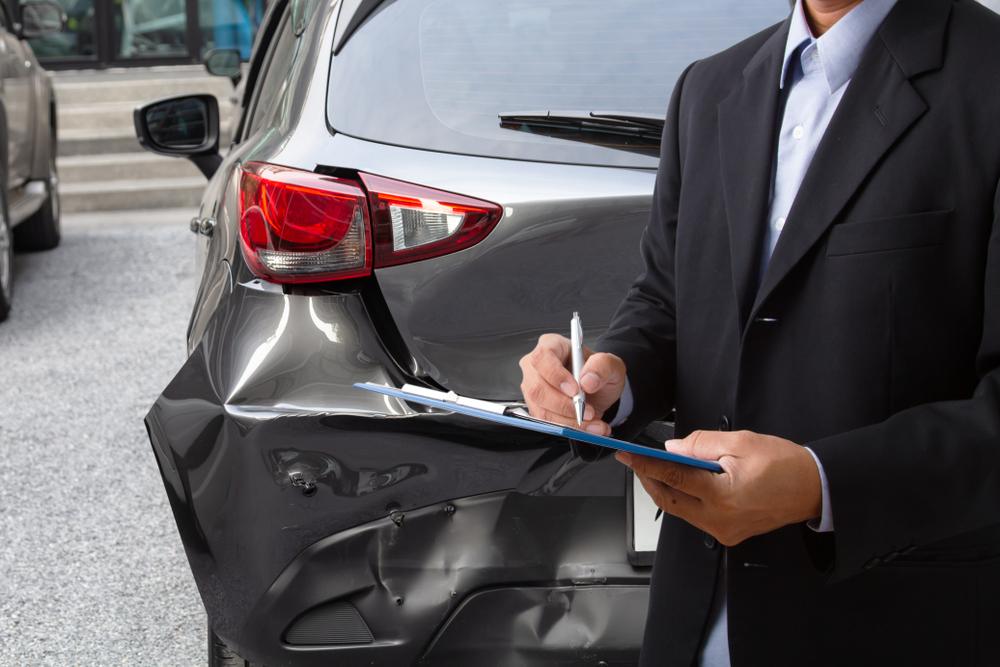 insurance officer looking at rear bumper damaging
