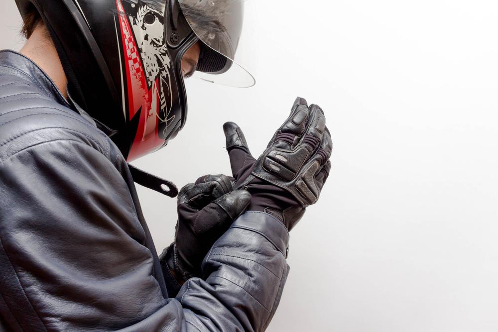 man putting on motorcycle gloves
