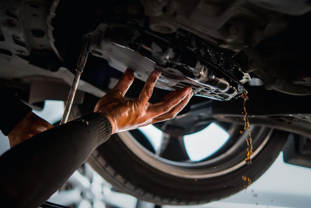 mechanic draining transmission fluid