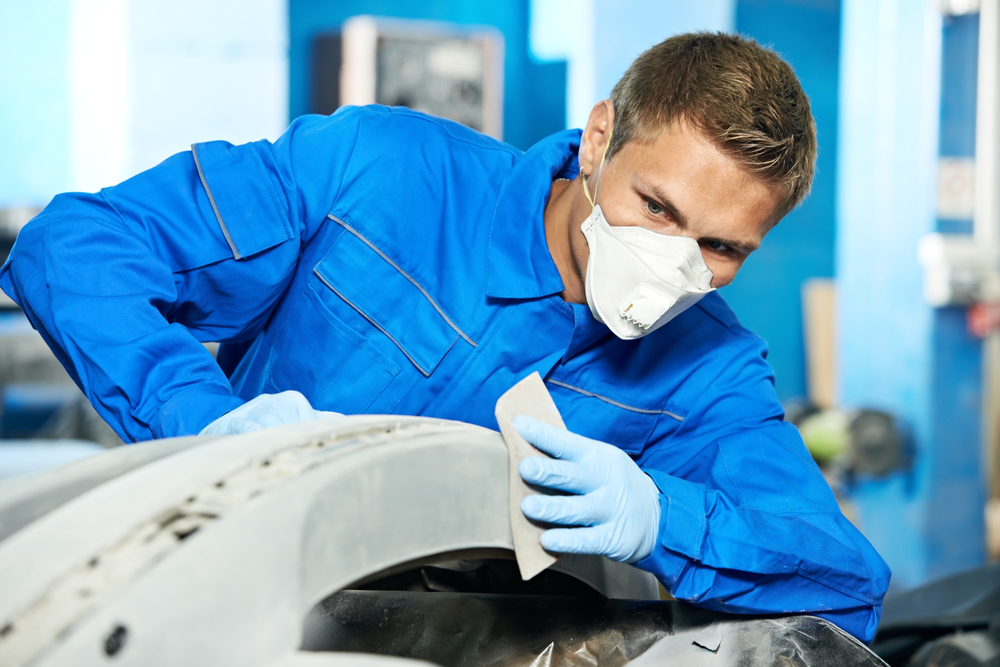 mechanic getting a rear bumper ready for installation