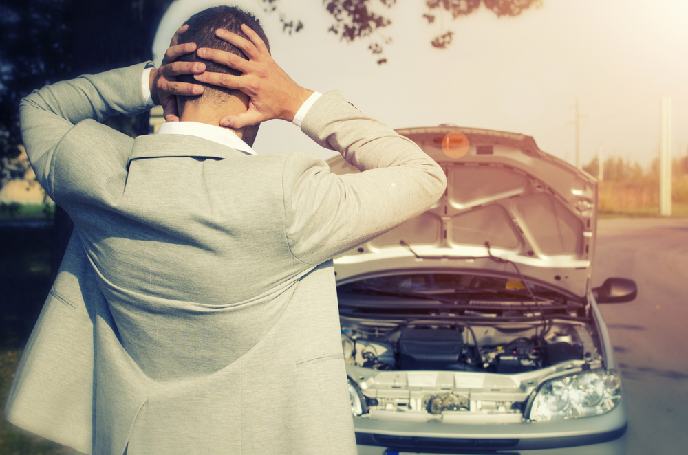 stressed man with smoking car and seized engine